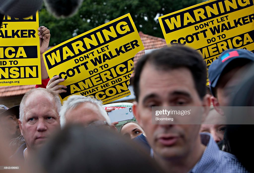 Demonstrators hold signs as <a gi-track='captionPersonalityLinkClicked' href=/galleries/search?phrase=Scott+Walker+-+Pol%C3%ADtico&family=editorial&specificpeople=7511934 ng-click='$event.stopPropagation()'>Scott Walker</a>, governor of Wisconsin and 2016 Republican presidential candidate, tours the Iowa State Fair in Des Moines, Iowa, U.S., on Monday, Aug. 17, 2015. Like most every other candidate in the historically crowded field, the Wisconsin governor's standing in state and national polls has been hurt by the summer surge of billionaire Donald Trump, the party's front-runner. Photographer: Daniel Acker/Bloomberg via Getty Images