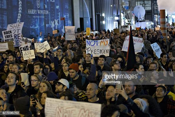 Demonstrators hold signs as they march from Union Square to Trump Tower during a rally against US Presidentelect Donald Trump in New York US on...