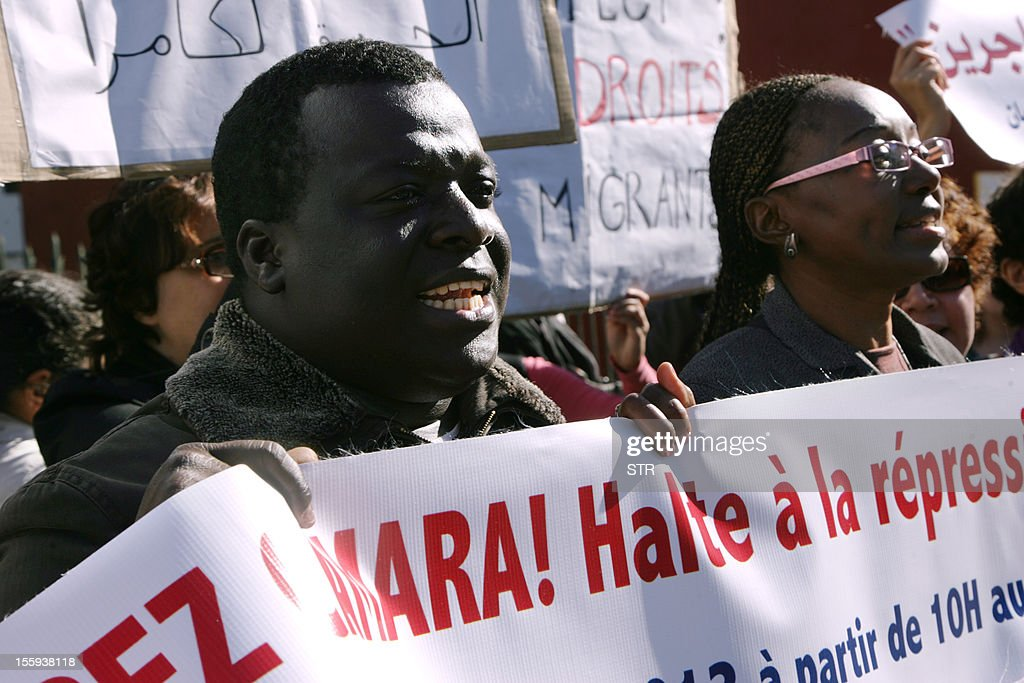 Demonstrators hold signs as they protest outside a court where Camara Laye, the founder of the Council of Sub-Saharan migrant in Morroco (CMSM) was being tried for illegally selling alcohol and cigarettes, on November 9, 2012 in Rabat. Laye was released on bail following an audience, on November 9, 2012. According to the police, Camara was arrested in the night of October 20 to October 21, 2012 as his home where police found three bottles of wine and two cartons of cigarettes.
