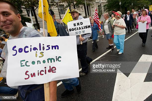 Demonstrators hold signs during a march by supporters of the conservative Tea Party movement in Washington on September 12 2010 Several thousand...
