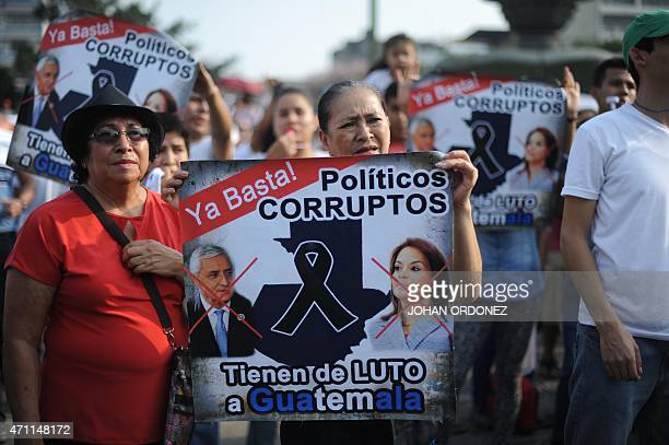 Demonstrators hold signs during a protest against Guatemalan President Otto Perez Molina and Vice President Roxana Baldetti for the recent corruption...