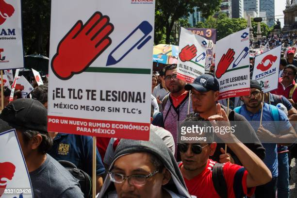Demonstrators hold signs during a protest against the North American Free Trade Agreement in Mexico City Mexico on Wednesday Aug 16 2017 US Trade...