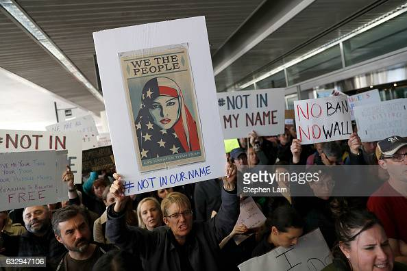 Demonstrators hold signs during a rally against a ban on Muslim immigration at San Francisco International Airport on January 28 2017 in San...