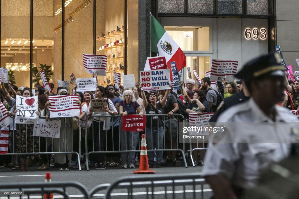 Demonstrators hold signs during the 'Defend DACA & TPS' rally outside of Trump Tower in New York, U.S., on Tuesday, Aug. 15, 2017. A day after belatedly faulting white supremacists for deadly clashes in Virginia, President Donald Trump returned to his controversial position that there was 'blame on both sides' for the weekend violence, saying that liberal counter-protesters also bore responsibility. Photographer: Jeenah Moon/Bloomberg via Getty Images