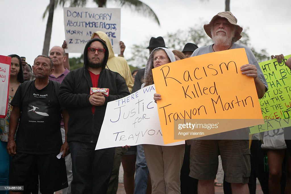 Demonstrators hold signs in front of the Torch of Friendship in downtown Miami a day after the verdict to the George Zimmerman murder trail on July 14, 2013 in Miami, Florida. A jury found neighborhood watch volunteer, George Zimmerman not guilty of shooting and killing 17-year-old Trayvon Martin after an altercation in February 2012.