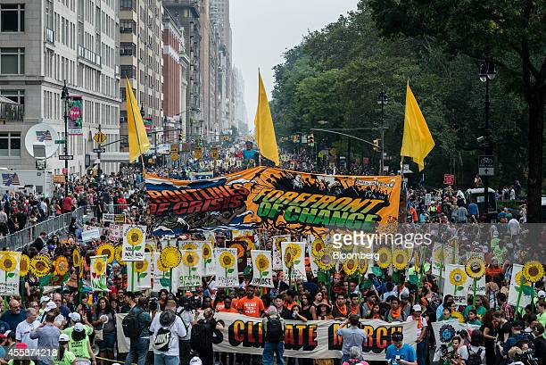 Demonstrators hold signs on a street next to Central Park during the People's Climate March in New York US on Sept 21 2014 The United Nations 2014...