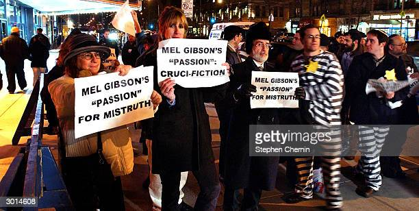 Demonstrators hold signs protesting Mel Gibson's The Passion of the Christ outside a movie theater February 25 2004 in New York CIty'The Passion of...