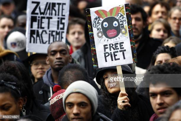 Demonstrators hold signs reading 'Black Pete is Rascism' and 'Free Black Pete' during a demonstration against Zwarte Piet in Amsterdam on November 16...