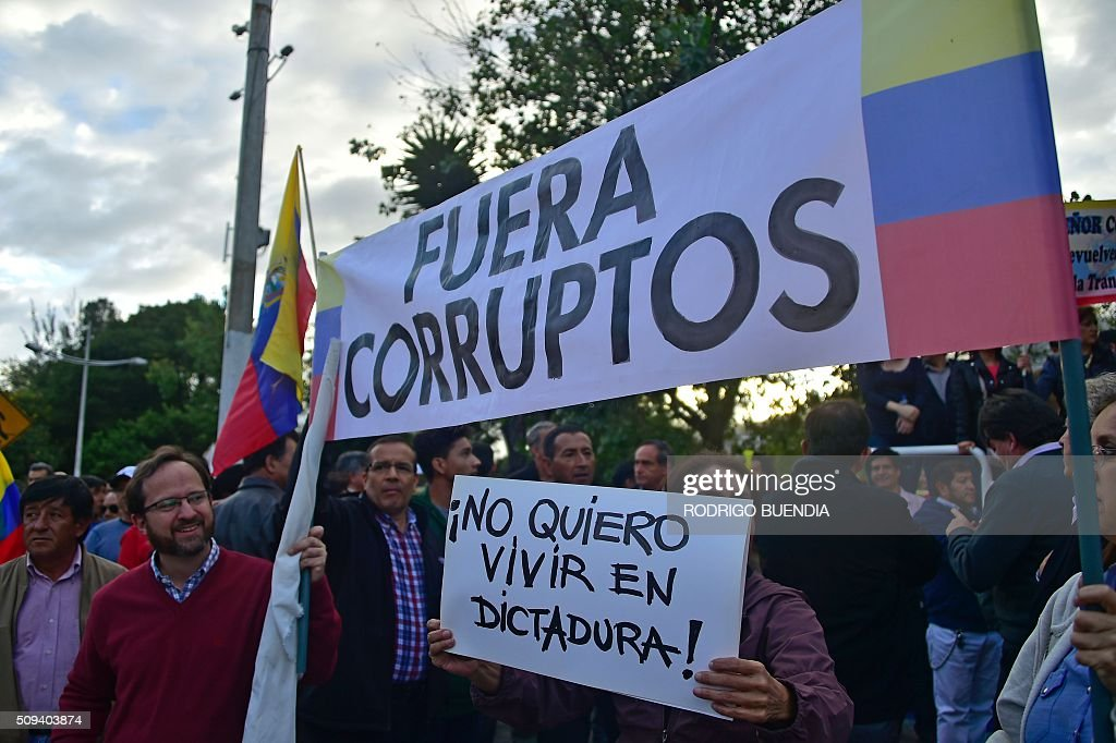 Demonstrators hold signs reading 'Out corrupts' and 'I don't want to live in a dictatorship!' as they protest against the government of Ecuadorean President Rafael Correa in Quito on February 10, 2016. AFP PHOTO / RODRIGO BUENDIA / AFP / RODRIGO BUENDIA