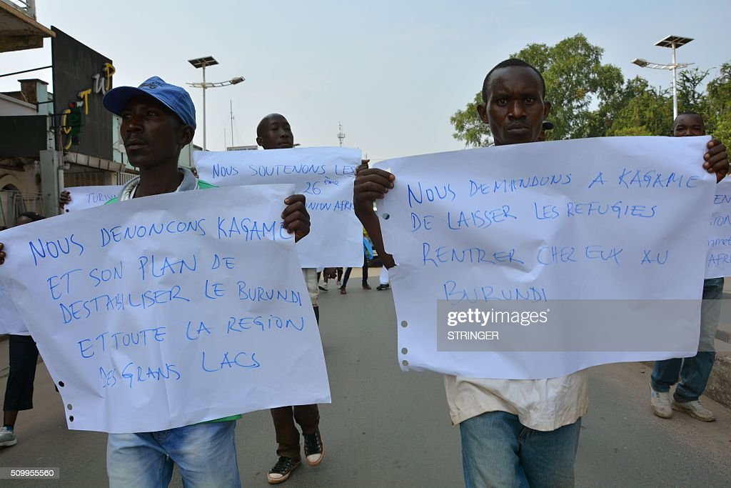 Demonstrators hold signs reading 'we ask Kagame to let the refugees come back home to Burundi' and 'We denounce Kagame's attempt to destabilise Burundi and the great lakes region' on February 13, 2016 in Bujumbura during a protest against Rwanda, in front of the Rwandan embassy. Rwanda is to relocate refugees from Burundi to other countries, amid accusations Kigali was meddling in the affairs of its troubled neighbour. UN experts told the Security Council that Rwanda has recruited and trained refugees from Burundi, among them children, who wanted to remove Burundi's President Pierre Nkurunziza from power. Burundi has repeatedly accused Rwanda of backing rebels intent on overthrowing the government in Bujumbura. Kigali has fiercely denied the accusations. Burundi has been in turmoil since Nkurunziza announced plans in April to run for a third term, which he went on to win. Hundreds of people have been killed and at least 230,000 have fled the country. Some 75,000 Burundian refugees are in Rwanda, according to the UN refugee agency, UNHCR. / AFP / STRINGER