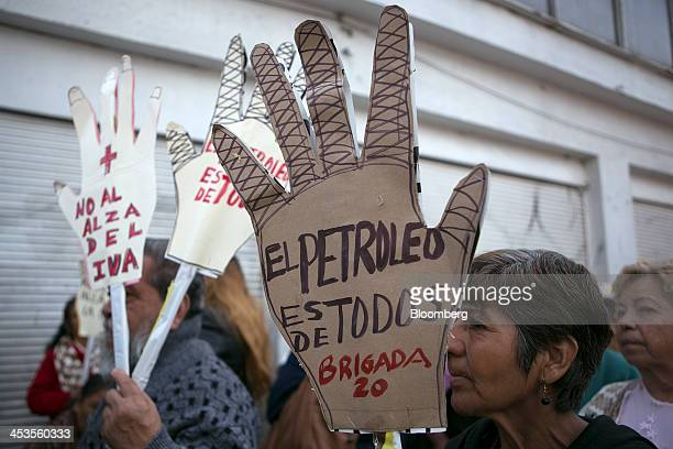 Demonstrators hold signs that read 'The oil belongs to everyone' front and 'No to increasing taxes' back near the Mexican Senate during a protest...