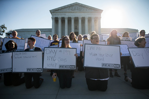 Demonstrators hold signs while gathering for a group photo during a demonstration urging the US Senate to hold a confirmation vote for Supreme Court...