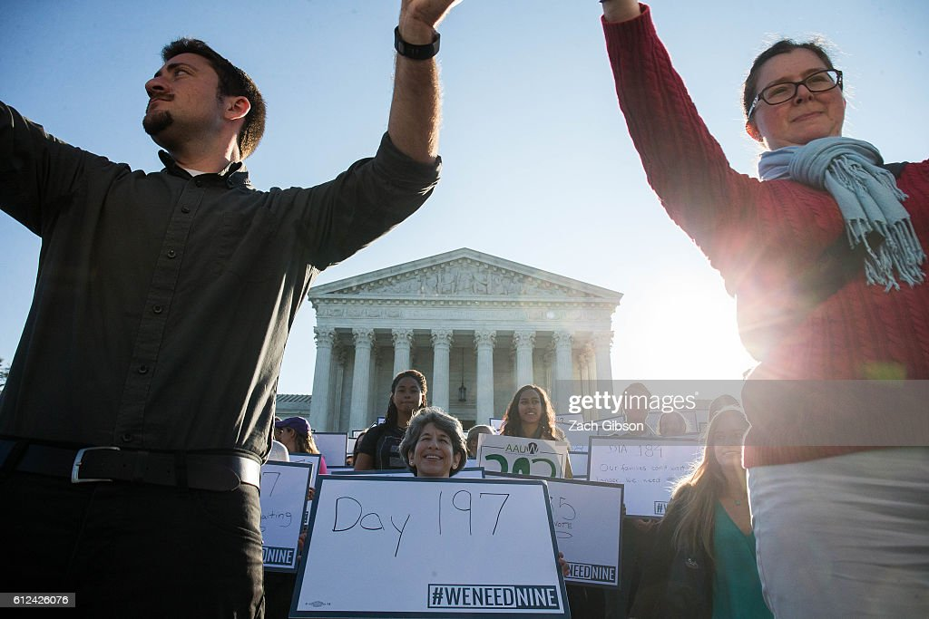 Demonstrators hold signs while gathering for a group photo during a demonstration urging the U.S. Senate to hold a confirmation vote for Supreme Court Nominee Merrick Garland outside of The Supreme Court of the United States on October 4, 2016 in Washington, DC. Today marks the 202nd day since President Barack Obama nominated Judge Garland to fill the vacancy left after former Justice Antonin Scalia passed away in February.