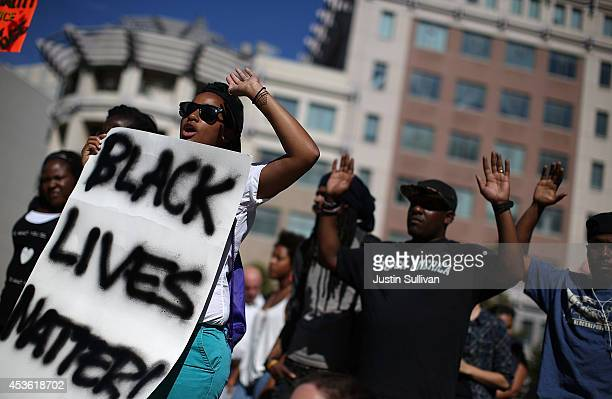 Demonstrators hold their hands up during a moment of silence on August 14 2014 in Oakland California Hundreds of demonstrators observed a national...