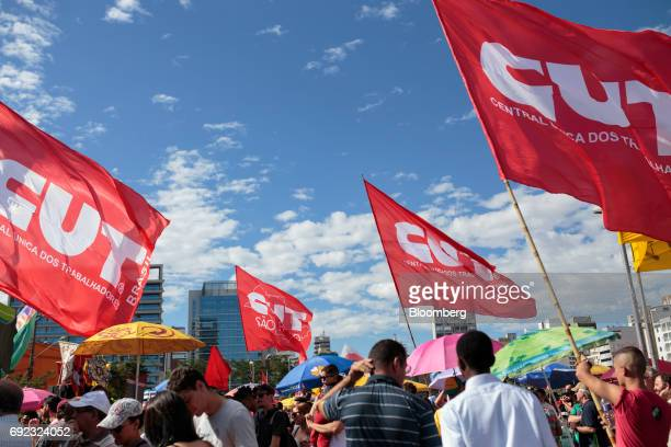 Demonstrators hold Unified Workers' Central flags during a protest against Brazilian President Michel Temer and government corruption at Largo da...