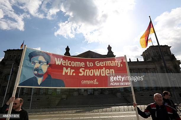 Demonstrators hold up a banner depicting fugitive US intelligence leaker Edward Snowden as they take part in a demonstration in favor of an...