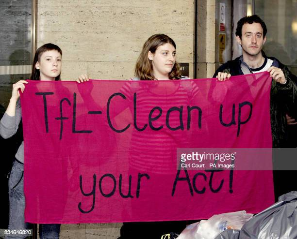 Demonstrators hold up a banner in St James Park underground station protesting against working conditions for contract cleaners on the London...