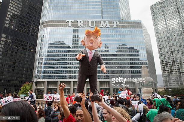 Demonstrators hold up a piñata of Republican Presidential candidate Donald Trump during a protest outside Trump Tower on October 12 2015 in Chicago...