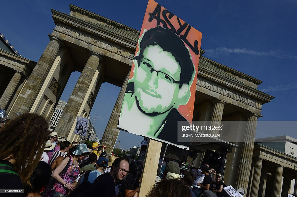Demonstrators hold up a placard in support of former US agent of the National Security Agency Edward Snowden in front of Berlin's landmark...