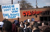 Demonstrators hold up a placard near the CVS Pharmacy that at was looted and burned on Pennsylvania Avenue in Baltimore Maryland April 28 2015...