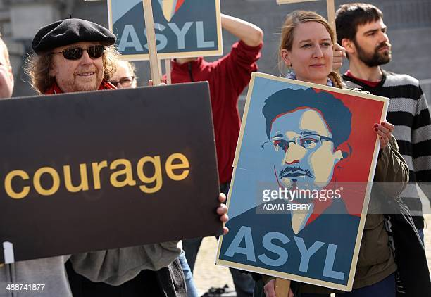 Demonstrators hold up a poster depicting fugitive US intelligence leaker Edward Snowden as they take part in a demonstration in favor of an...