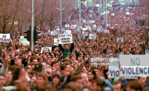 Demonstrators hold up placards 09 March as tens of thousands of ethnic Albanians gather in down town Pristina to hold a peaceful protest against the...