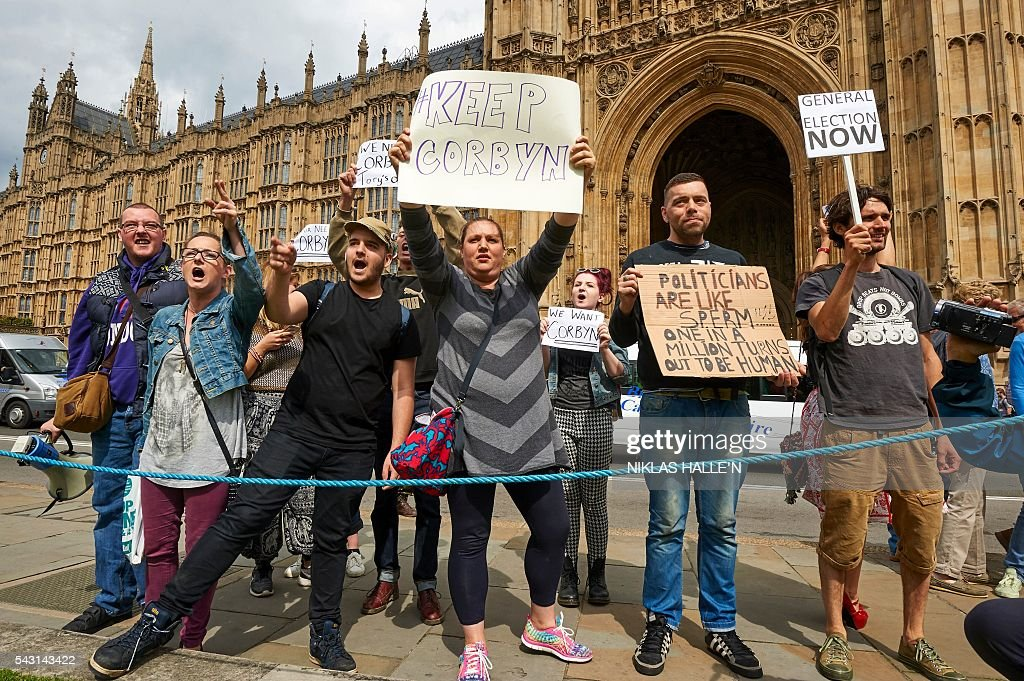 Demonstrators hold up placards as they protest outside the British Parliament in central London on June 26, 2016. Britain's opposition Labour party plunged into turmoil Sunday and the prospect of Scottish independence drew closer, ahead of a showdown with EU leaders over the country's seismic vote to leave the bloc. Two days after Prime Minister David Cameron resigned over his failure to keep Britain in the European Union, Labour leader Jeremy Corbyn faced a revolt by his lawmakers who called for him, too, to quit. / AFP / Niklas HALLE'N