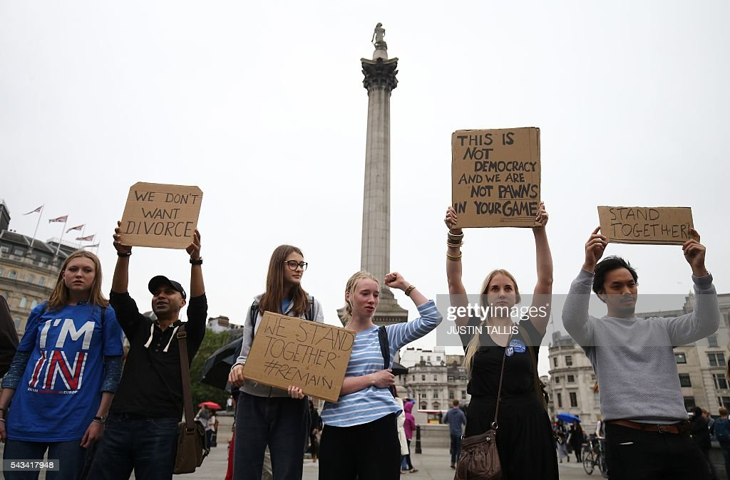 Demonstrators hold up placards with slogans against the split with the EU at an anti-Brexit protest in Trafalgar Square in central London on June 28, 2016. EU leaders attempted to rescue the European project and Prime Minister David Cameron sought to calm fears over Britain's vote to leave the bloc as ratings agencies downgraded the country. Britain has been pitched into uncertainty by the June 23 referendum result, with Cameron announcing his resignation, the economy facing a string of shocks and Scotland making a fresh threat to break away. / AFP / JUSTIN