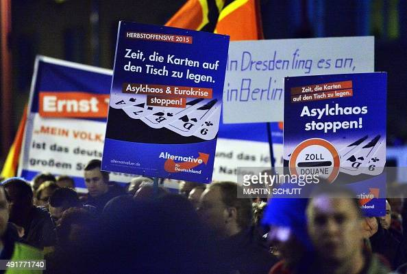 Demonstrators hold up posters reading 'Stop the Asylum Chaos and the Euro Crisis' as they protest against the German government's asylum policy on...