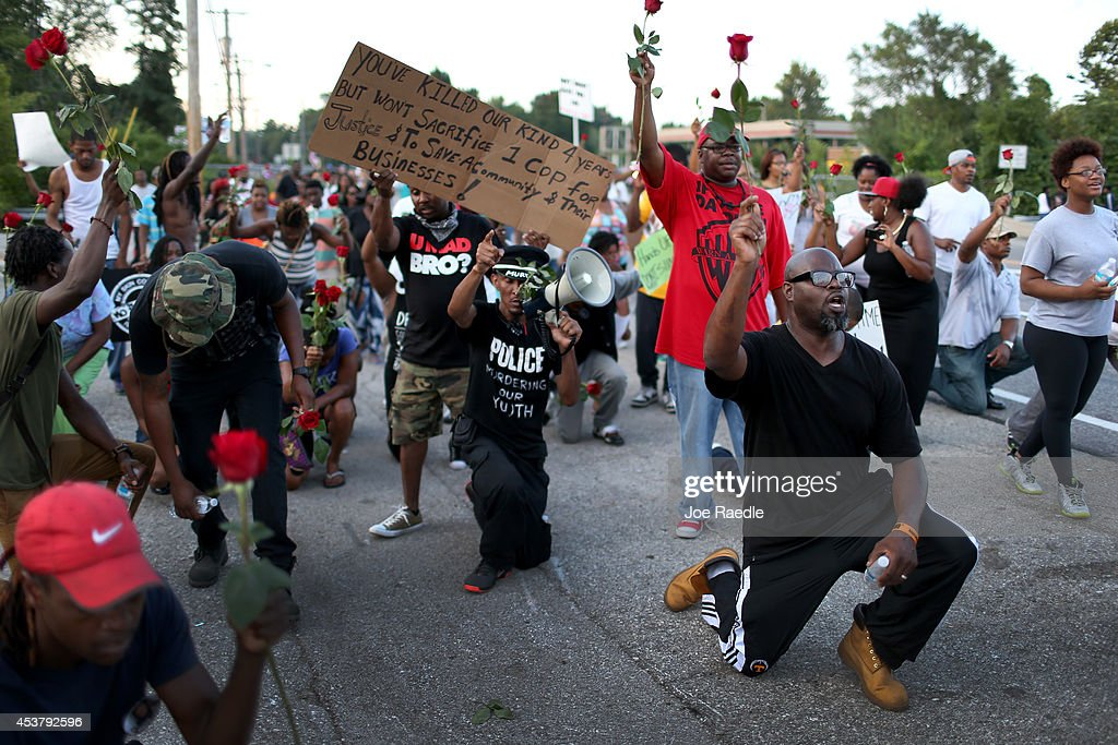 Demonstrators hold up roses while protesting the shooting death of Michael Brown make their voices heard on August 18, 2014 in Ferguson, Missouri. Protesters have been vocal asking for justice in the shooting death of Michael Brown by a Ferguson police officer on August 9th.