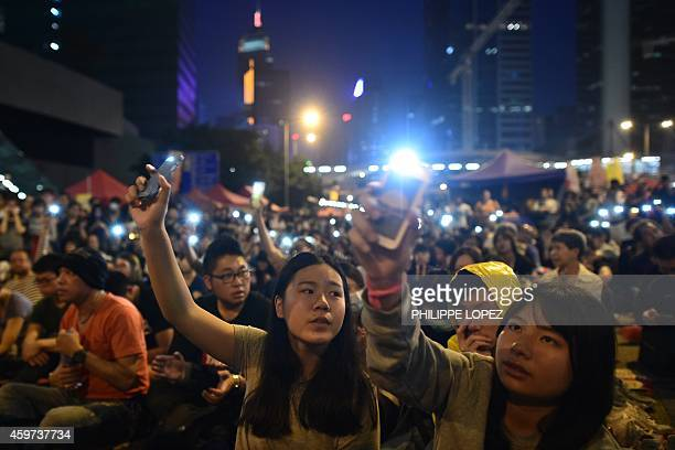 Demonstrators hold up their mobile phones on an occupied road during a prodemocracy rally in the Admiralty district of Hong Kong on November 30 2014...