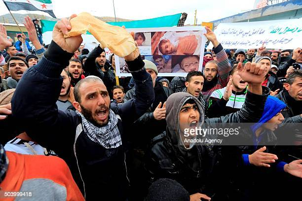 Demonstrators holding breads chant slogans against Syrian regime and Hezbollah during a protest remarking the humanitarian crisis in Syria's Madana...
