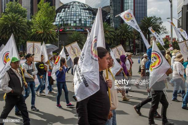Demonstrators holding flags walk past the Mexican Stock Exchange during a protest against the North American Free Trade Agreement in Mexico City...