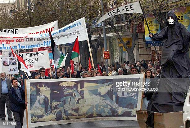 Demonstrators holding Iraqi and Palestinian flags carry a banner showing Guernica by Pablo Picasso during an antiwar protest 20 March 2004 in...