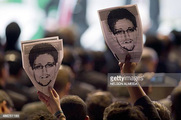 Demonstrators holding papers to be cut to make portraits of Edward Snowden protest during the opening ceremony during the opening ceremony of the...