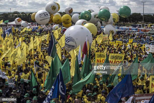 Demonstrators holding signs and flags gather during protests outside of the National Congress demanding the resignation of President Michel Temer in...