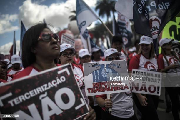 Demonstrators holding signs gather during protests outside of the National Congress demanding the resignation of President Michel Temer in Brasilia...