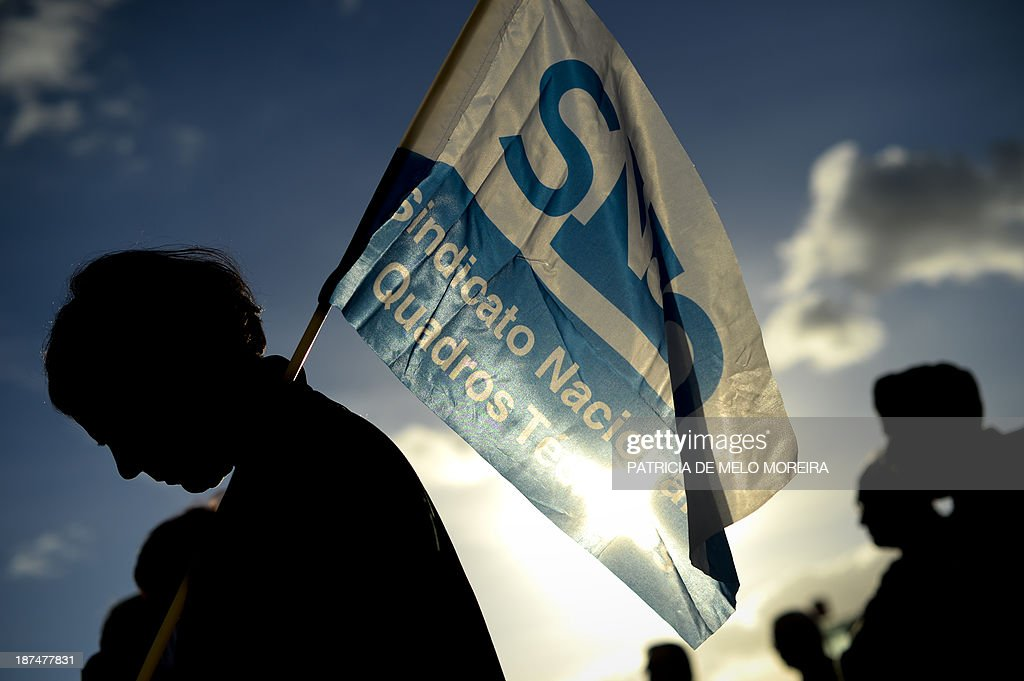 A demonstrators holds a flag during a protest called by the Portuguese Federation of Transportation and Communication Unions (FECTRANS) against austerity measures and the government's 2014 draft budget, in Lisbon on November 9, 2013. Hundreds of people protested against planned reductions in transport workers' pay as well as the privatisation of public sector projects. AFP PHOTO / PATRICIA DE MELO MOREIRA
