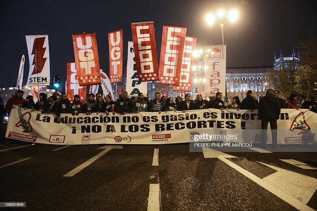 Demonstrators holds a giant banner reading 'Education is not spending, it is investment. No to the cuts!' during a protest against government's austerity reforms and cuts in Madrid on December 13, 2012. Public spending on education has been cut by more than a billion euros this year compared with 2011, and public schools employed nearly 3,000 fewer teachers during the 2011-12 academic year, according to the education ministry.