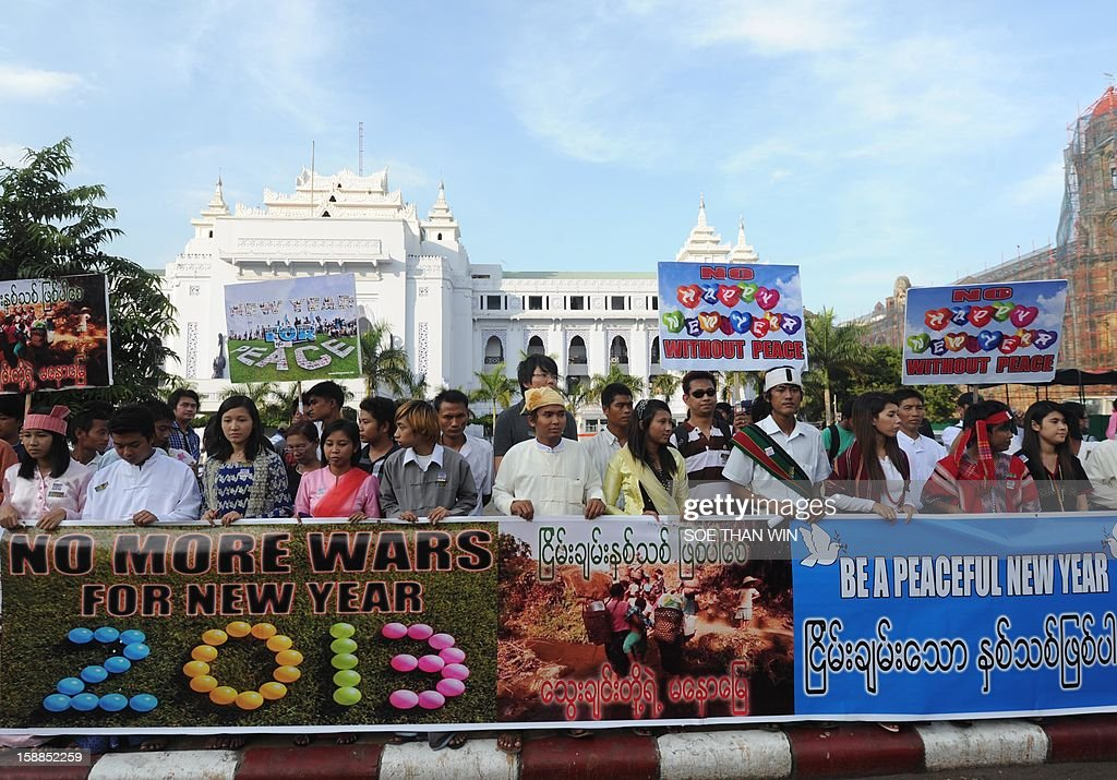 Demonstrators holds banners during a protest against civil war in the country, in Yangon on January 1, 2013. Protesters rallied in downtown Yangon demanding an end to civil war in Myanmar. AFP PHOTO/ Soe Than WIN