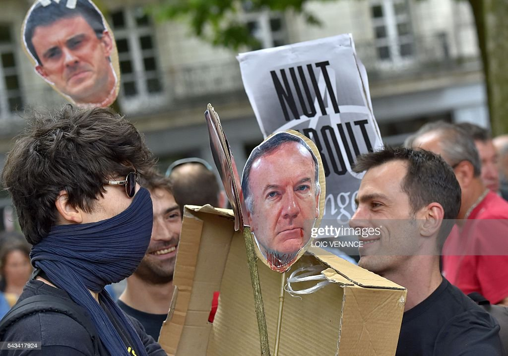 Demonstrators holds portraits of French Prime Minister Manuel Valls (L) and French employers' association Medef president Pierre Gattaz (R) during a protest against controversial labour reforms, on June 28, 2016 in Nantes, western France. People took to the streets in France on June 28 in the latest protest march in a marathon campaign against the French Socialist government's job market reforms. Last month the government used a constitutional manoeuvre to push the bill through the lower house without a vote in the face of opposition from Socialist backbenchers. / AFP / LOIC