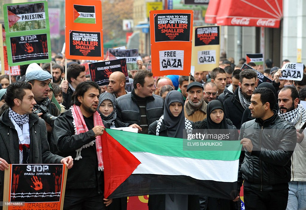 Demonstrators holds up posters and a Palestinian flag during a march on November 20, 2012, through the center of Sarajevo in support of Palestinian people following the latest Israeli attacks in Gaza. Israel's air force dropped leaflets across Gaza City on Tuesday urging people to evacuate their homes 'immediately' amid fears the military was poised to launch a ground operation. The violence comes as Israel heads towards a general election in January, raising the spectre of a broader Israeli military campaign along the lines of its devastating 22-day Operation Cast Lead launched at the end of December 2008.