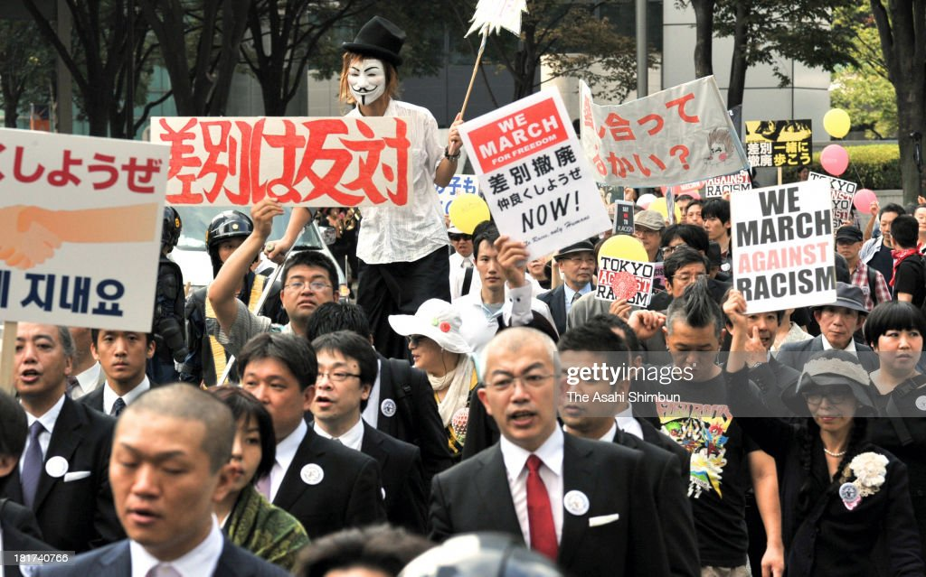 Demonstrators in black suits lead a march against discrimination on September 22, 2013 in Tokyo, Japan. The March on Tokyo for Freedom was organized mainly by the People's Front of Anti-Racism, an organization that has scuffled with anti-Korea protesters in Koreatown in the Shin-Okubo district of Shinjuku ward.