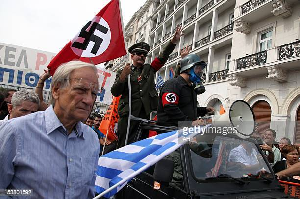 Demonstrators in mock Nazi garb ride in a vehicle in Athens during a demonstration against the vist of the German Chancellor Angela Merkel on October...