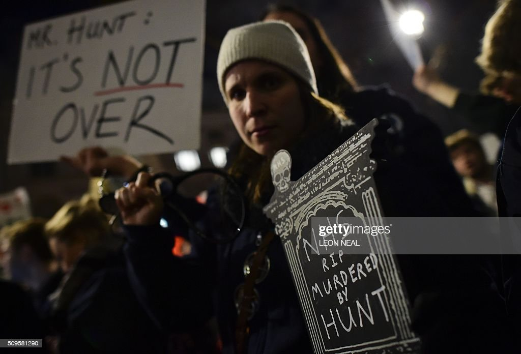 Demonstrators including junior doctors gather with placards outside the Department of Health on Whitehall in central London on February 11, 2016, to protest following the annoucement of the government decision to impose new contracts on junior doctors. Britain's government said February 11 it would impose new contracts on junior doctors to force an end to strikes over changes to their working conditions. Health Secretary Jeremy Hunt told the House of Commons that the decision had been taken after negotiations with doctors' union the British Medical Association (BMA) failed. The announcement came after nearly three years of negotiations and the day after a second 24-hour strike led to nearly 3,000 operations being postponed in England. NEAL