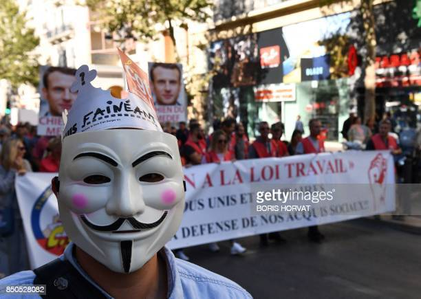 Demonstrators including one wearing a 'Guy Fawkes' mask with the word translated as 'lazy' march behind a banner during a rally in Marseille on...
