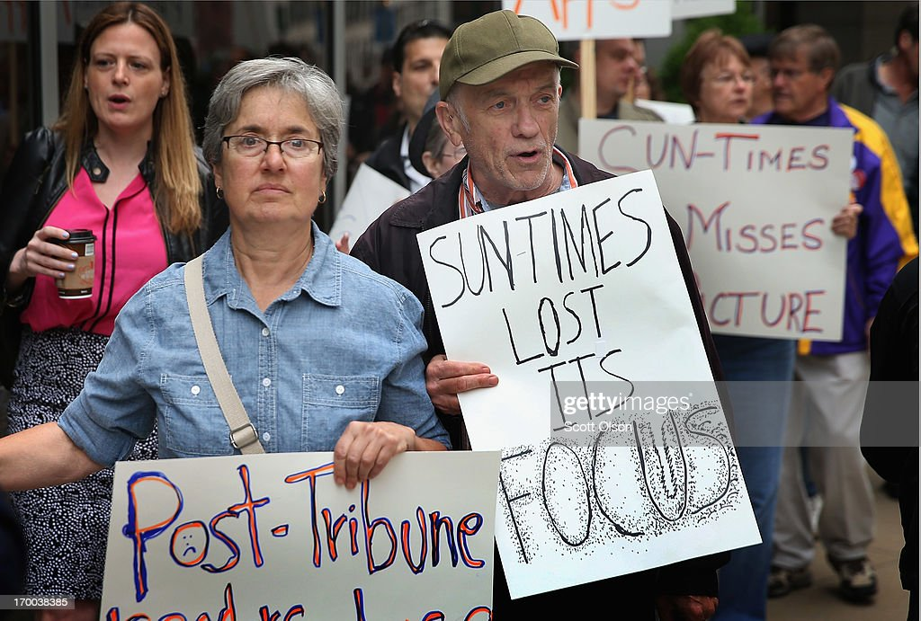 Demonstrators, including union members, reporters, and photographers march outside the offices of the Chicago Sun-Times protesting the newspapers decision to eliminate its 28-member photography staff on June 6, 2013 in Chicago, Illinois. The newspaper chain plans to train their reporters to take pictures with iPhones to fill the void.
