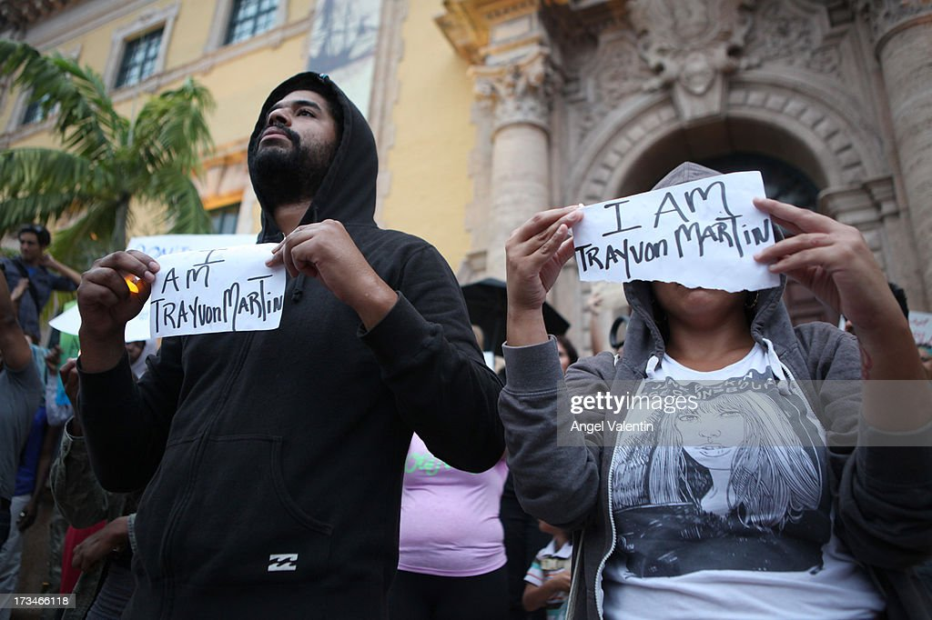 Demonstrators James Alvarez, 34, and Yesenia Mena, 29, hold signs in front of the Freedom Tower in downtown Miami a day after the verdict to the George Zimmerman murder trail on July 14, 2013 in Miami, Florida. A jury found neighborhood watch volunteer, George Zimmerman not guilty of shooting and killing 17-year-old Trayvon Martin after an altercation in February 2012.