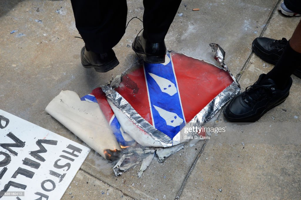 Demonstrators jump on an Confederate flag replica in reaction to a potential white supremacists rally on August 18, 2017 in Durham, North Carolina. The demonstration comes a week after a fatal clash during a 'Unite the Right' rally between white supremacists and counter protesters in Charlottesville, Virginia.