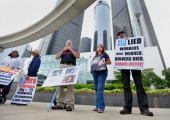 Demonstrators Ken Rimer from third left Laura Christian and Frank Hammer hold signs in front of General Motors Co headquarters at the GM Renaissance...